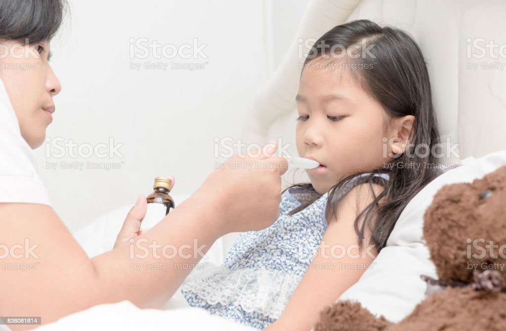 Asian Mother giving her daughter  syrup because of the flu stock photo