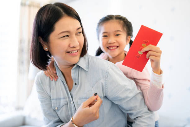 asian mother giving red envelope to daughter - chinese new year stock pictures, royalty-free photos & images