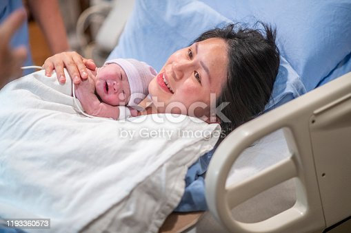 A young Asian mother lays in her hospital bed in the delivery room after giving birth to her son.  She has him laying on her chest as the share an intimate moment together and some skin-to-skin time.  She is wearing a blue hospital gown and has a white blanket draped over the newborn.