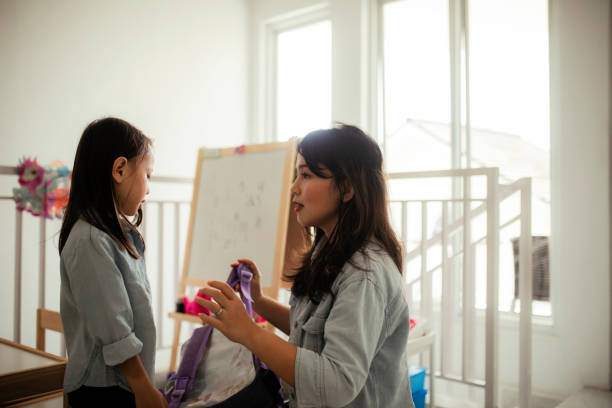 Asian mother helping daughter get ready for school stock photo