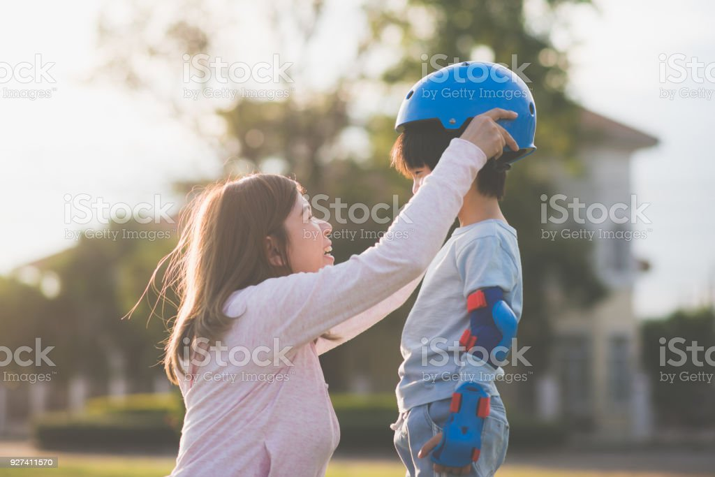 Asian mother helping her son wears blue helmet on enjoying time together in the park royalty-free stock photo
