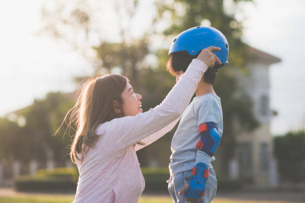 asian mother helping her son wears blue helmet on enjoying time together in the park - protection stock photos and pictures
