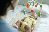 istock Asian Mother holding her son legs while baby boy lying on bed playing with mobile. 1303504345