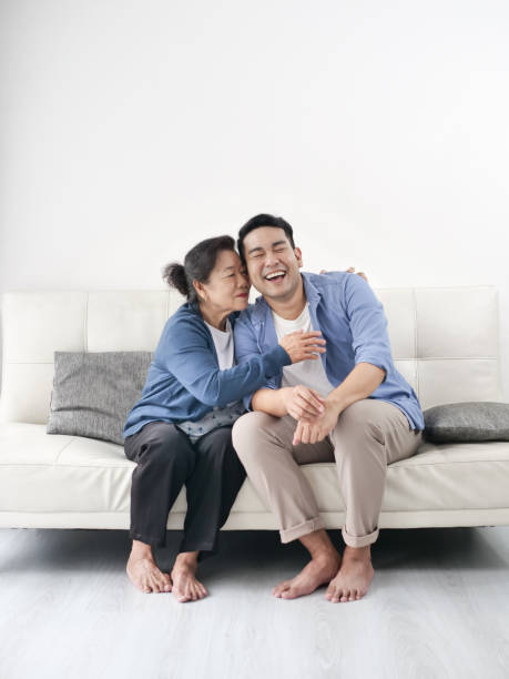 Asian mother hugging her son and sitting on sofa at home, lifestyle concept. Asian mother hugging her son and sitting on sofa at home, lifestyle concept. old mother son asian stock pictures, royalty-free photos & images