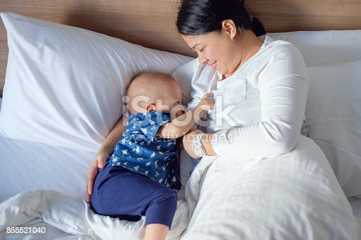 1049923194 istock photo Asian mother is breastfeeding Cute little Asian 14 months / 1 year old toddler baby boy child in bed 855521040