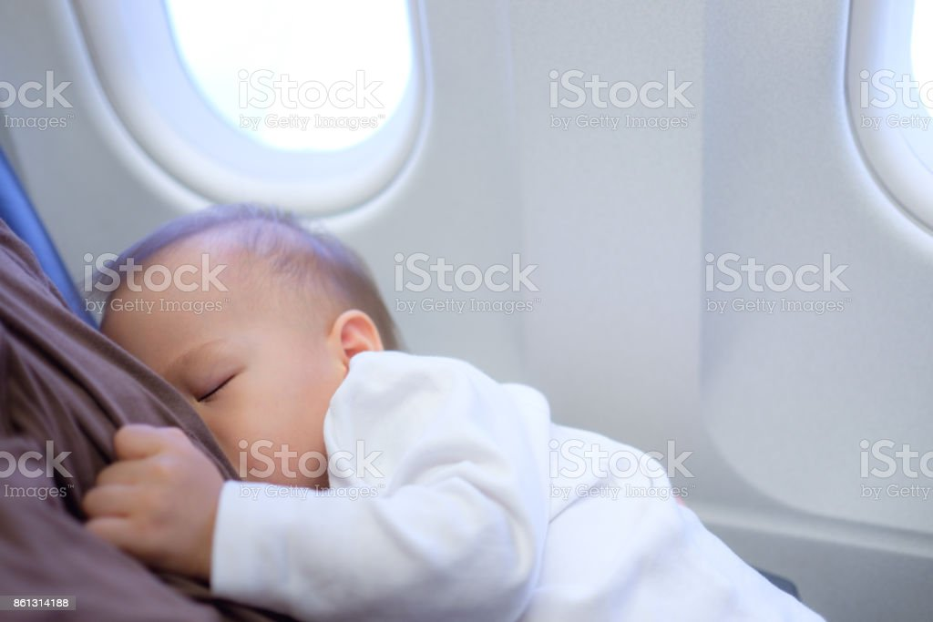Asian mother is breastfeeding Cute little Asian 18 months toddler baby boy child on Airplane stock photo