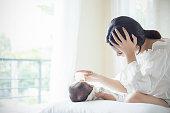 妊娠中のうつ病から苦しんでベッドの中で新生児にフォーミュラミルクのアジアの母保育園給餌ボトル。ヘルスケアシングルママ母性ストレスの概念.