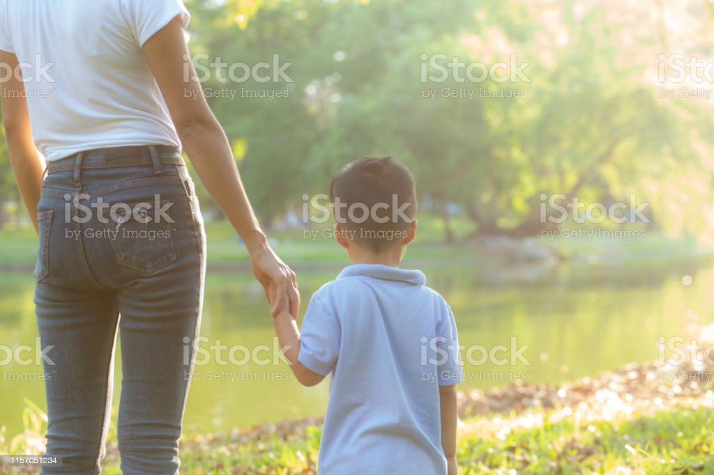 Asian mother or parent and son holding hand with love together in...
