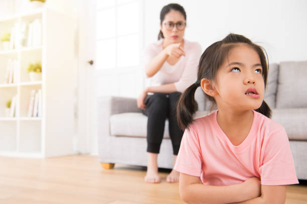 asian mother sitting on the sofa angry pointing stock photo