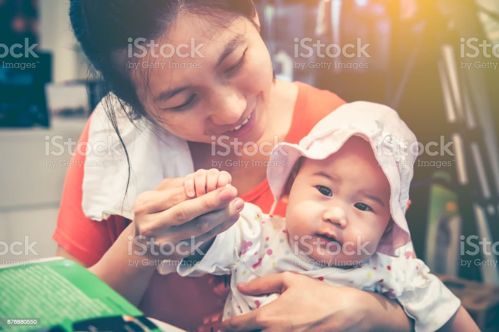 Asian mother smiling and take care her daughter with love. Vintage tone. stock photo