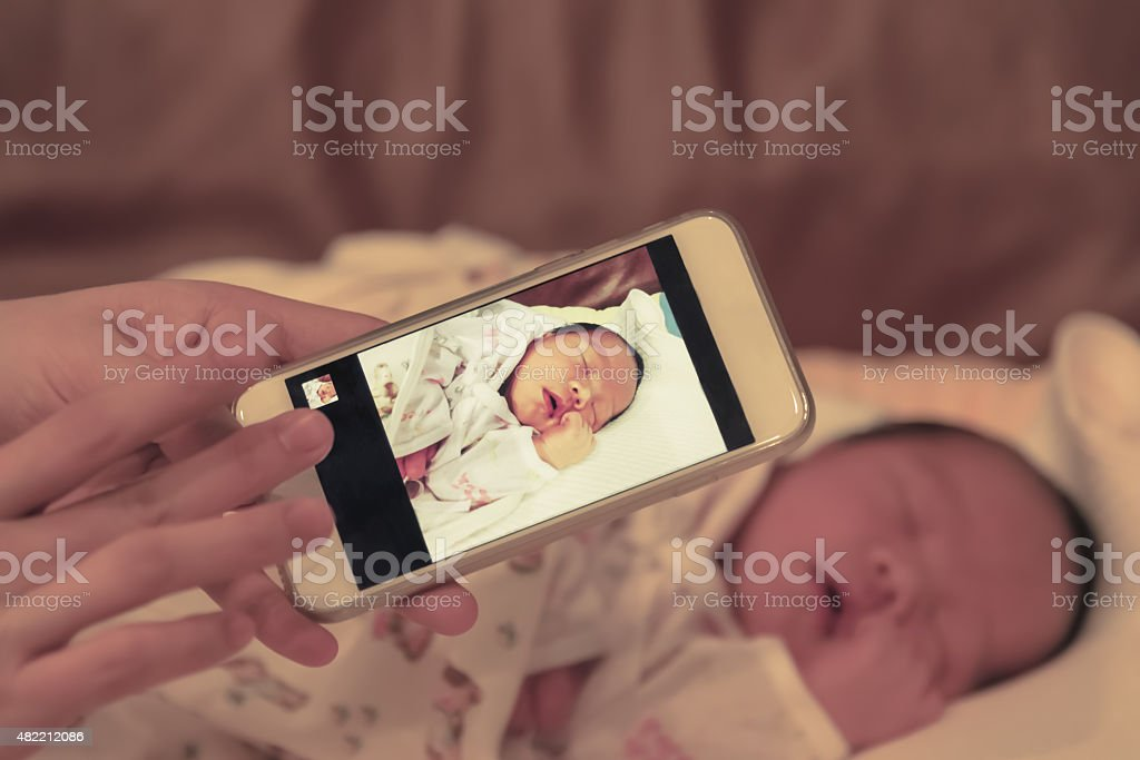 Asian mother take a photo of her baby with smartphone stock photo
