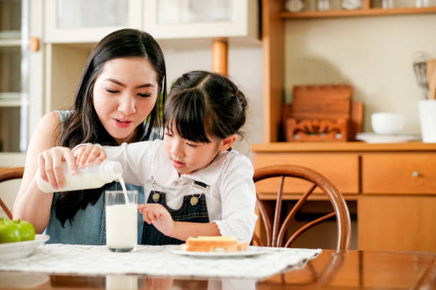 412 Mother Pouring Milk For Children In Kitchen Stock Photos, Pictures &  Royalty-Free Images - iStock