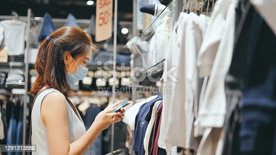 Asian mother use smartphone compare price between Online Sale and Outlet sale for choosing cheapest in shopping mall
