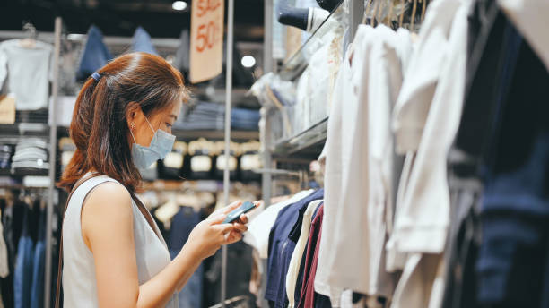 Asian mother use smartphone compare price between Online Sale and Outlet sale for choosing cheapest in shopping mall stock photo
