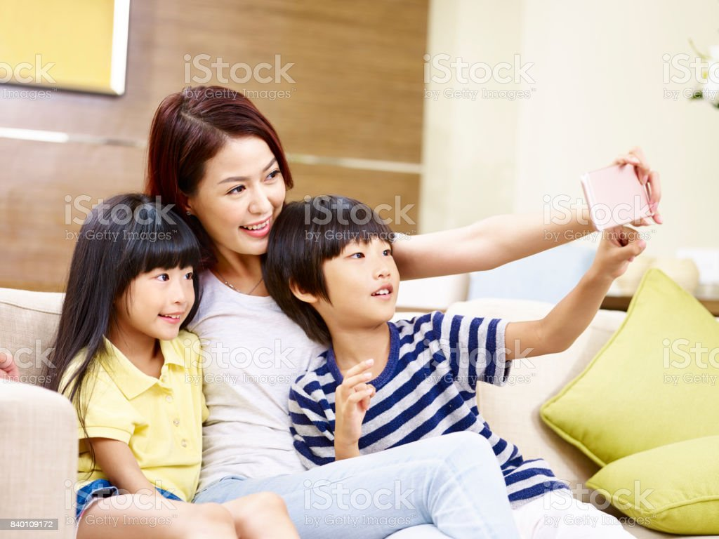 asian mother with two children taking a selfie stock photo