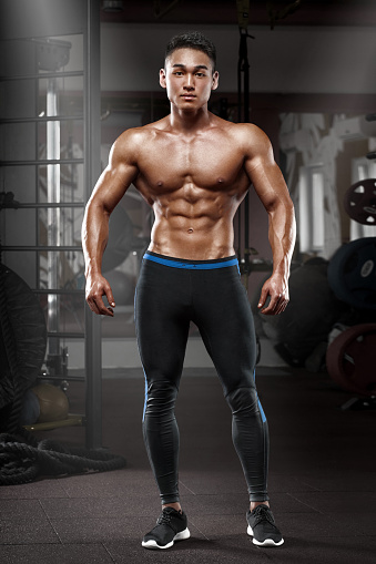 Bodybuilder showing his back and biceps muscles, personal fitness trainer. Strong man