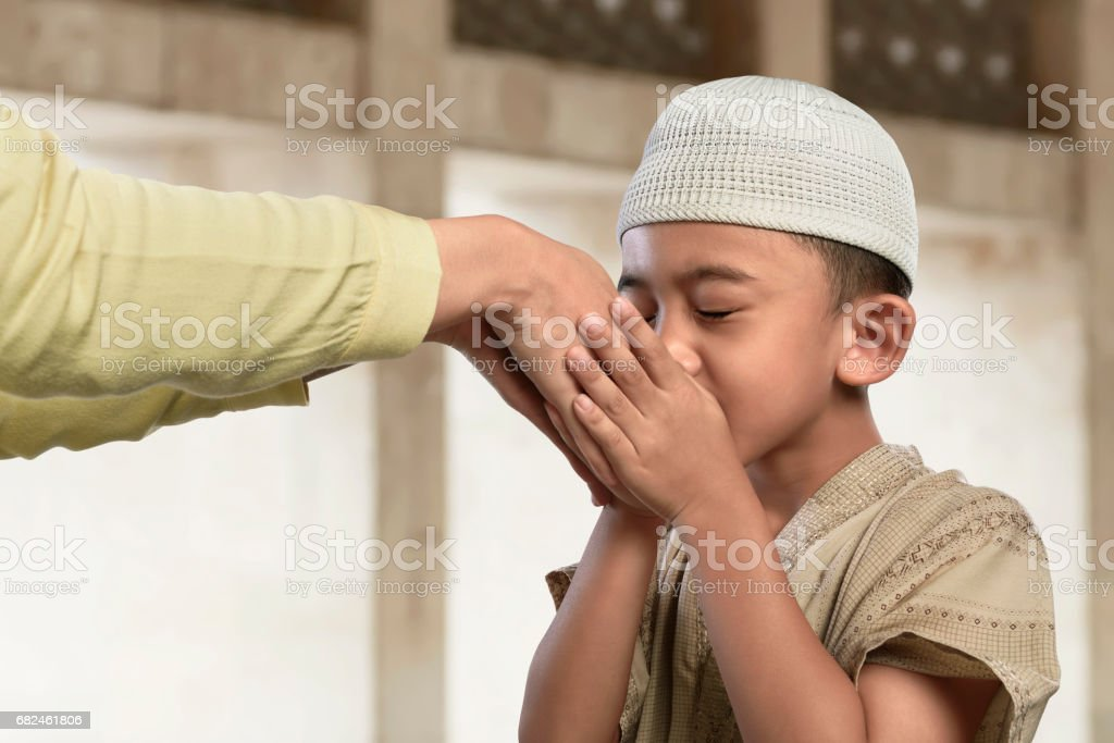 Asian muslim child kissing a hand from an old people stock photo