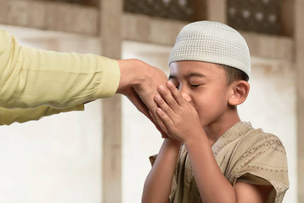asian muslim child kissing a hand from an old people - eid stock pictures, royalty-free photos & images