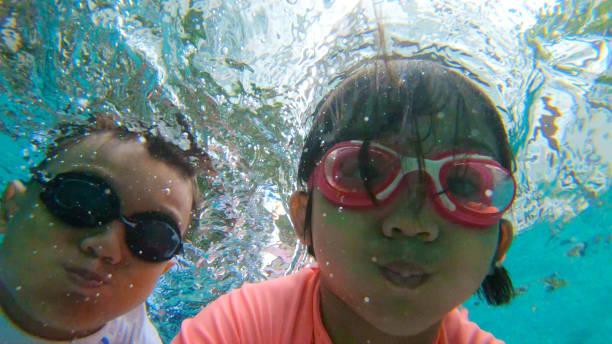 Asian Muslim Children Swimming in an Apartment Pool stock photo