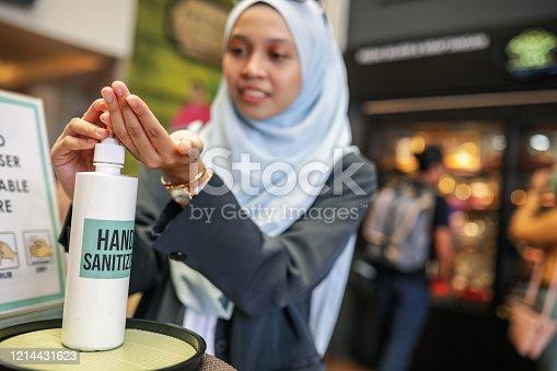 Asian muslim corporate women washing hand using sanitiser
