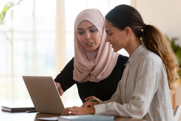 asian muslim female mentor teaching caucasian intern explaining computer work - скромная одежда стоковые фото и изображения