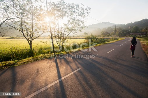 Asian Muslim girl walks alone early in the morning on the empty road