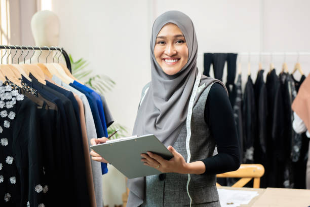 Asian muslim woman designer in her tailor shop Happy smiling Asian muslim woman designer as a startup business owner working in her tailor shop indonesian ethnicity stock pictures, royalty-free photos & images