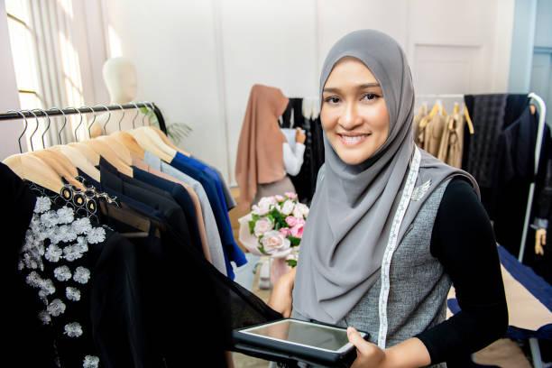 Asian muslim woman designer in her tailor shop stock photo