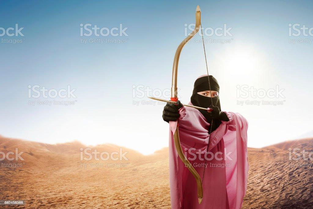 Asian muslim woman in veil ready to shoot an arrow royalty-free stock photo
