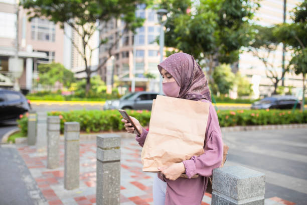 asian muslim woman using phone when walking on the street stock photo