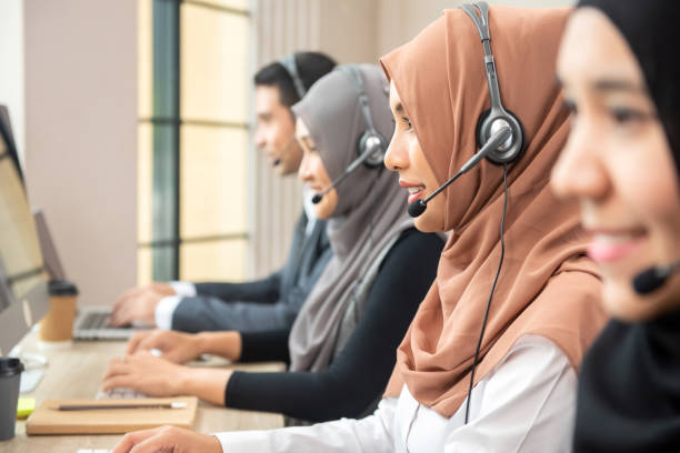 Asian muslim women working  in call center with team stock photo