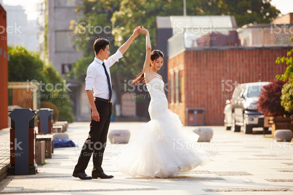 asian newlywed dancing outdoors stock photo
