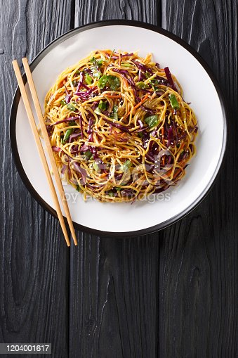 Asian Noodle Salad with thinly sliced red cabbage, julienned carrots in spicy peanut dressing close-up in a plate on the table. Vertical top view from above