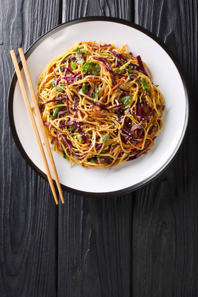 Asian Noodle Salad with thinly sliced red cabbage, julienned carrots in spicy peanut dressing close-up in a plate. Vertical top view stock photo