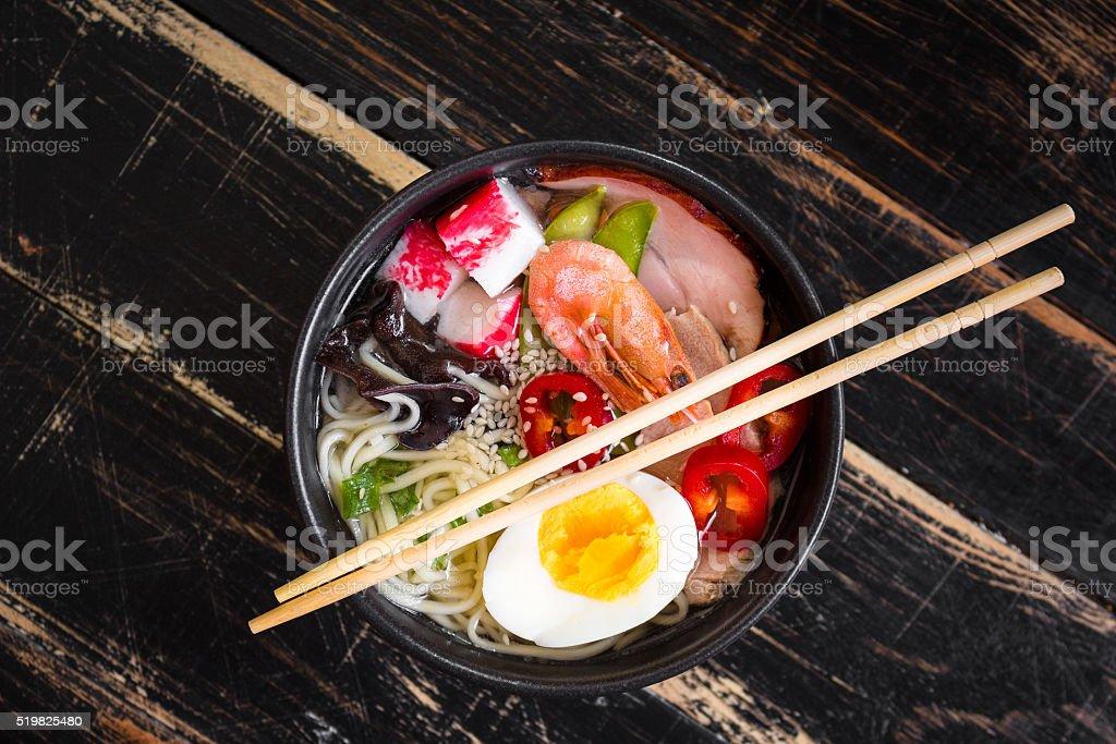 Asian noodle soup in a black bowl stock photo