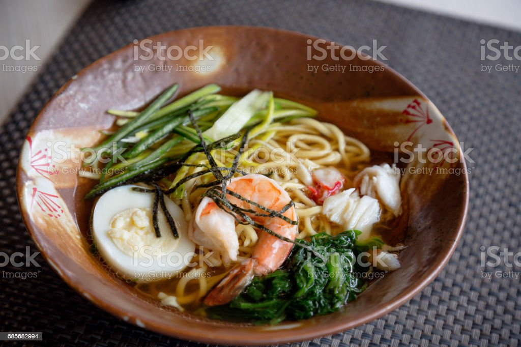 Asian noodle soup with crap meat, boiled egg, shrimp, spinach. Closeup with selective focus foto de stock royalty-free