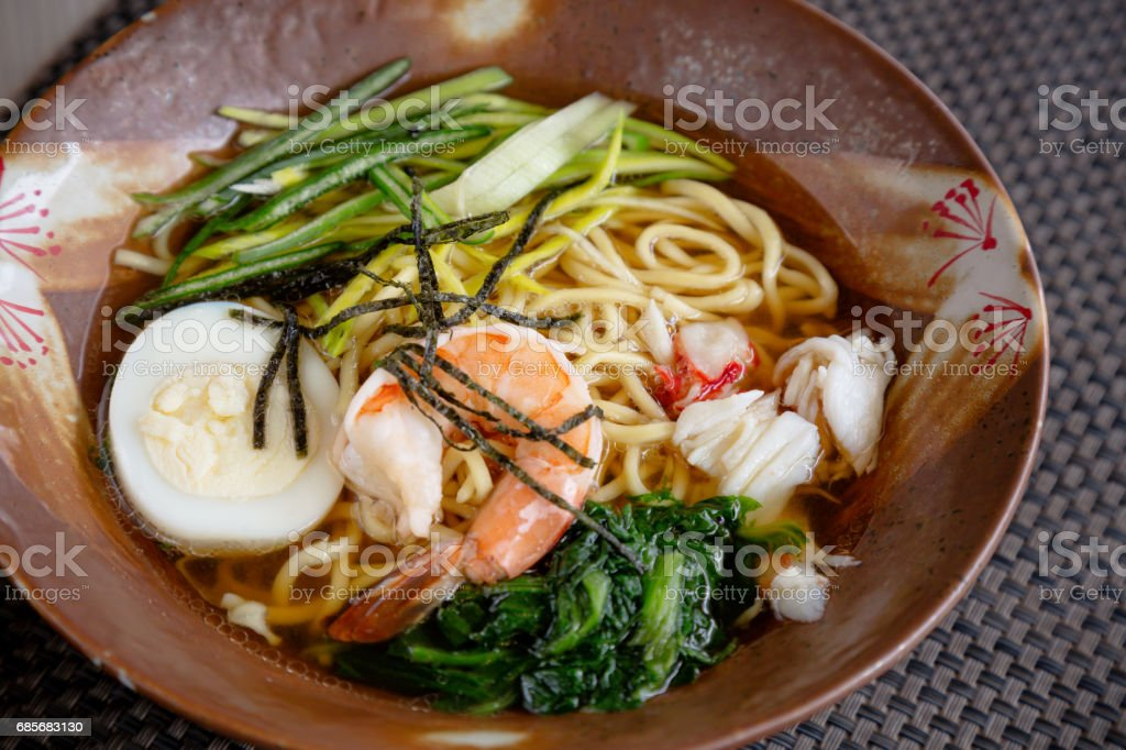 Asian noodle soup with crap meat, boiled egg, shrimp, spinach. Closeup with selective focus royalty-free stock photo