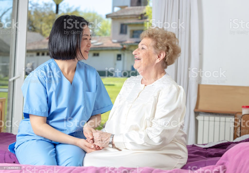 Asian nurse assisting elderly lady in hospital.