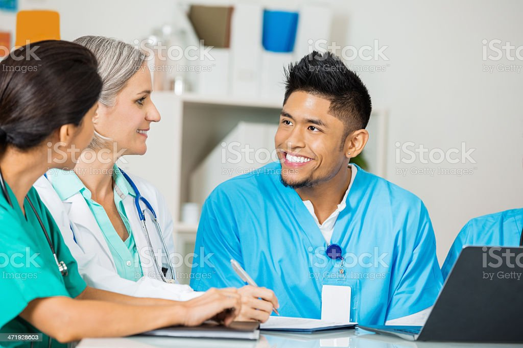 Asian nurse or doctor discussing policy changes during staff meeting