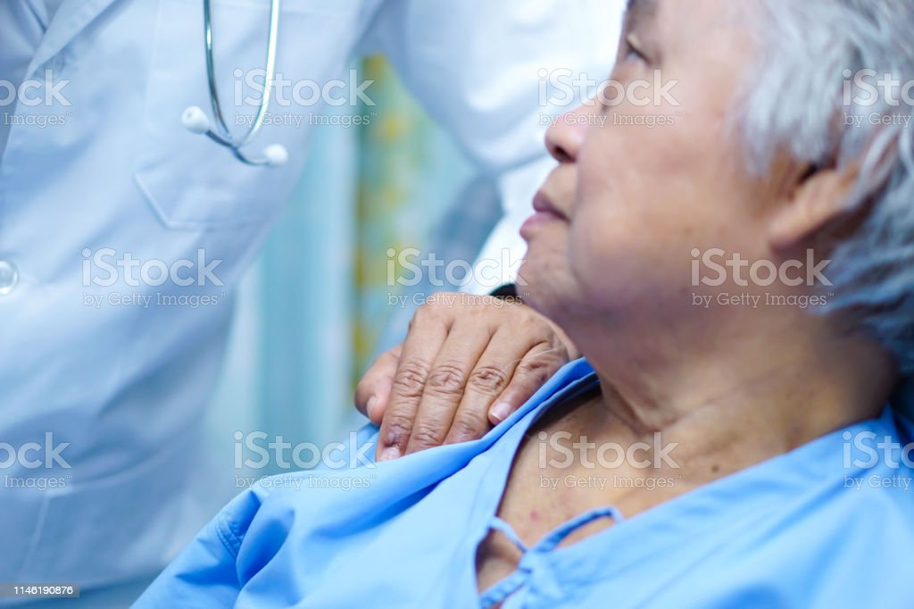 Asian nurse physiotherapist doctor touching Asian senior or elderly...