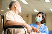 istock Asian nurse taking care of mature male patient sitting on wheelchair in hospital. Young woman and old man wearing surgical face mask for protection of The COVID pandemic. Girl talking to elderly man. 1279835139