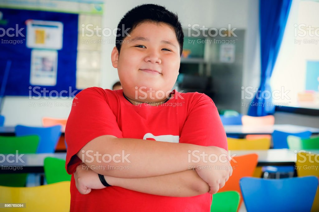 Asian obese boy standing crossed arms and cute smile stock photo