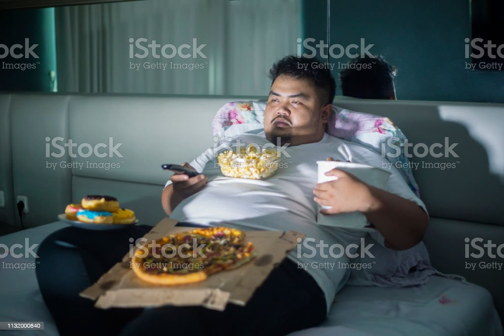 Asian obese man eating junk foods while watching TV in bed before...