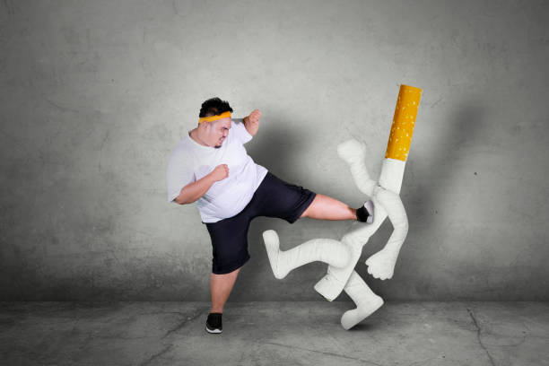 Asian obese man kicking a cigarette stock photo