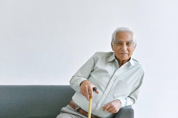 Asiatische alte Mann, zuversichtlich und lächelnd eisern auf weißem Hintergrund, Senioren halten Unterstützung Rohr zur Verbesserung der beweglichen Fähigkeit, Glückliche Rentner Bürger Konzept. – Foto