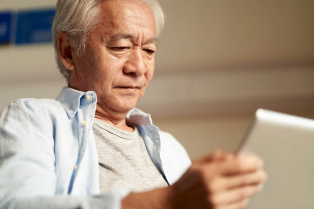 asian old man looking at digital tablet stock photo
