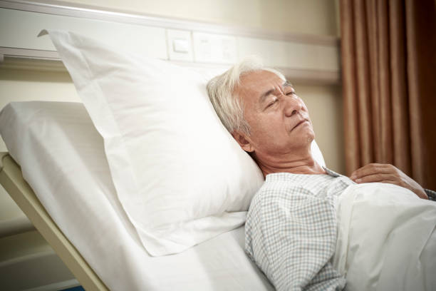 asian old man lying on back on hospital bed stock photo