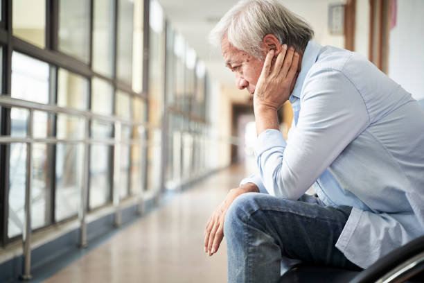 asian old man sitting in hospital hallway looking sad and depressed stock photo