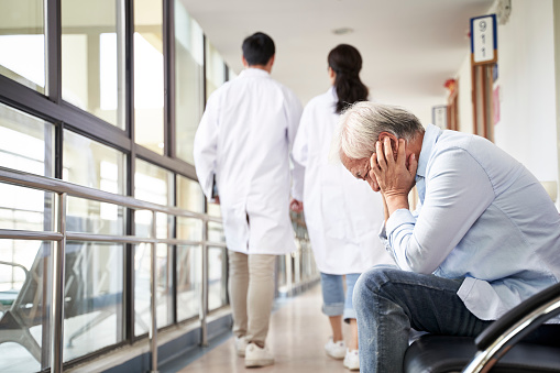 1049772134 istock photo asian old man sitting in hospital hallway looking sad and depressed 1209378132