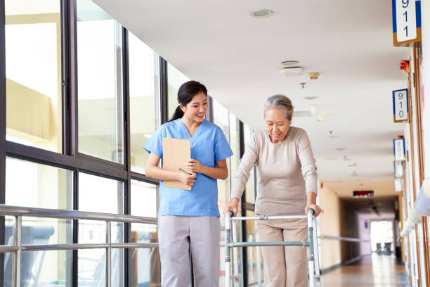asian old patient walking using walker in rehabilitation center stock photo